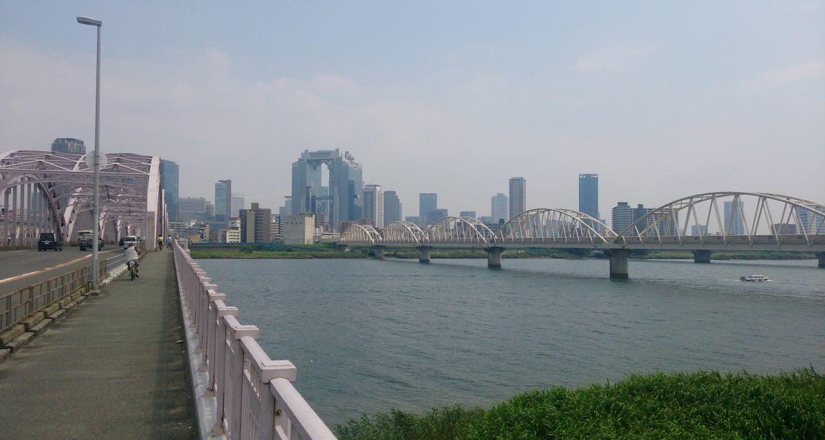 よく晴れた暑い午後に淀川大橋を歩いて渡る